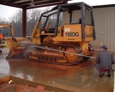 Using a de-mucking system on a dirty bulldozer.